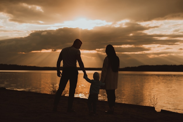 Silhouette of a family with their son on the beach in summer by the river