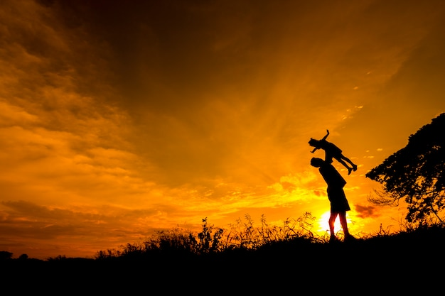 Silhouette of father and daugther on a mound at sunset.