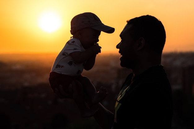 Silhouette of a father holding up his baby.