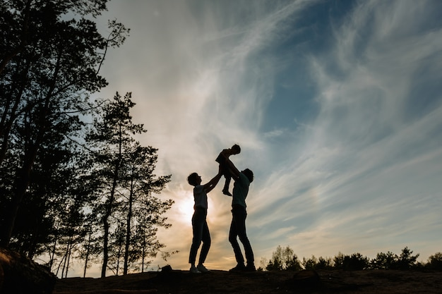 The silhouette of a father and mother raising their son above them against the background of the sunset
