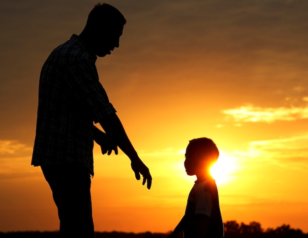 A silhouette of father and son play on sunset