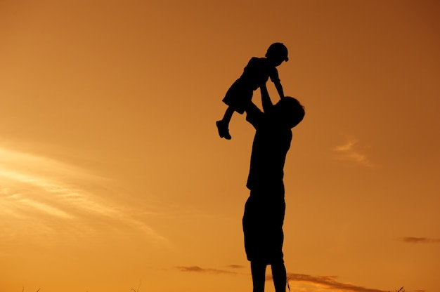 Silhouette of a father and son playing outdoors at sunset