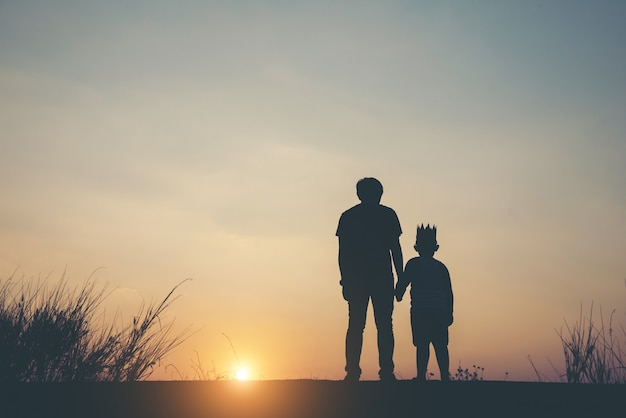 Silhouette of father and son standing together.