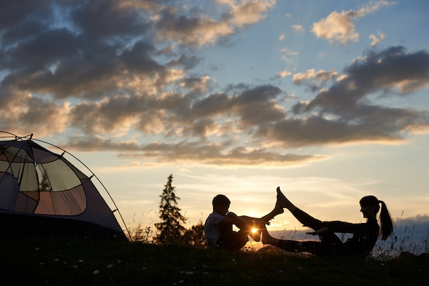 Silhouette of female and boy sitting on the grass in a yoga pose at daybreak near a tent.