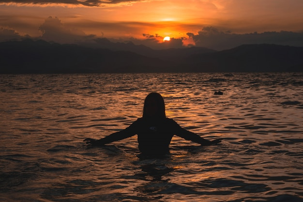 Silhouette of a female half in the water of a sea during a beautiful sunset