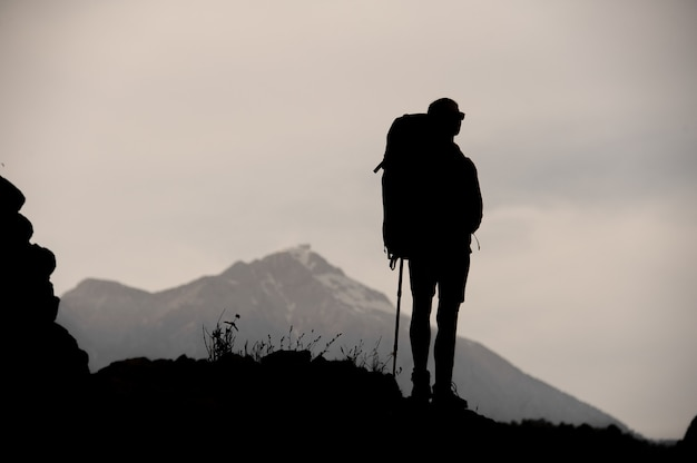 Silhouette of female hiker standing on top of mountain