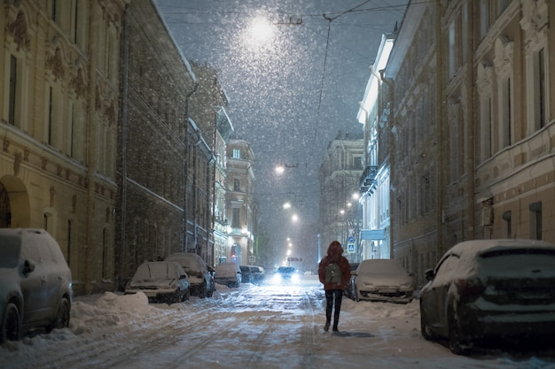 Silhouette of female walking along parked cars on empty evening city street during a snowfall