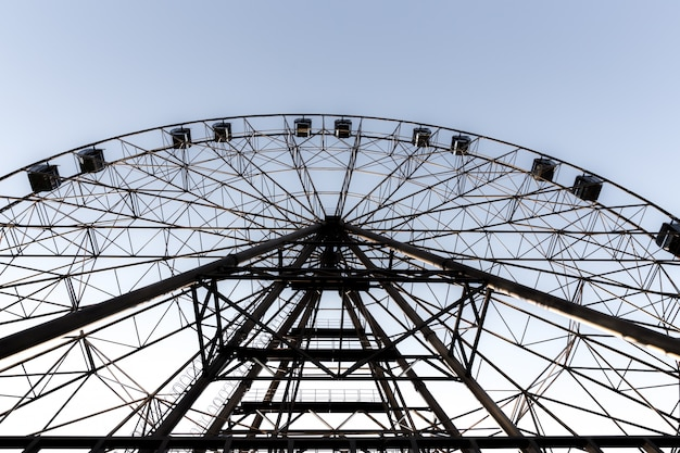 Silhouette of ferris wheel on the background of blue sky