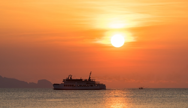 Silhouette of a ferry ship with beautiful sunset background