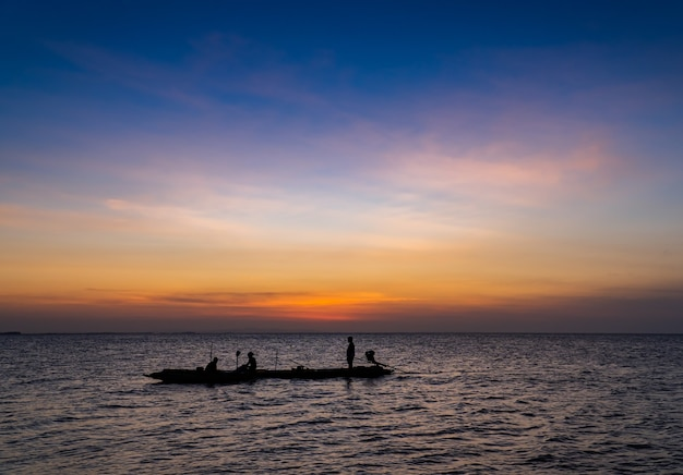 Silhouette fisherman on boat on sunset sky in the evening