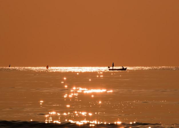 朝は自然に輝く黄金の海を釣り上げるシルエット漁師