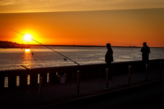 Silhouette of fisherman over sunset in city port.
