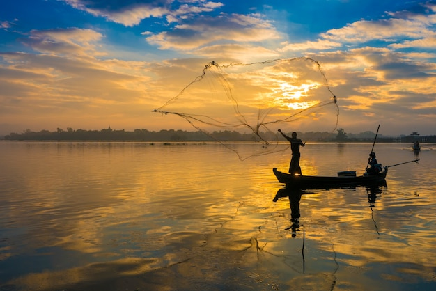 The silhouette of fisherman throwing net in the early morning