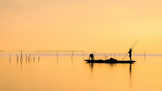 Silhouette of fisherman on traditional boat in lake in morning