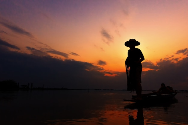Silhouette fisherman with sunset
