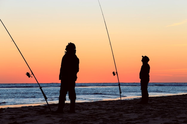 Silhouette of the fishermen on the beach at sunrise