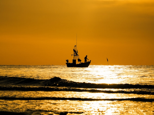 Silhouette fishermen in a boat on sunset sea