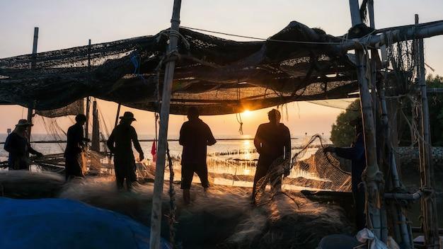 シルエットの漁師がネットを引っ張って、タイのサムットプラカンにあるバンプー港で日没時にアザラシの魚を手に入れます。地元の漁村での仕事と職業。