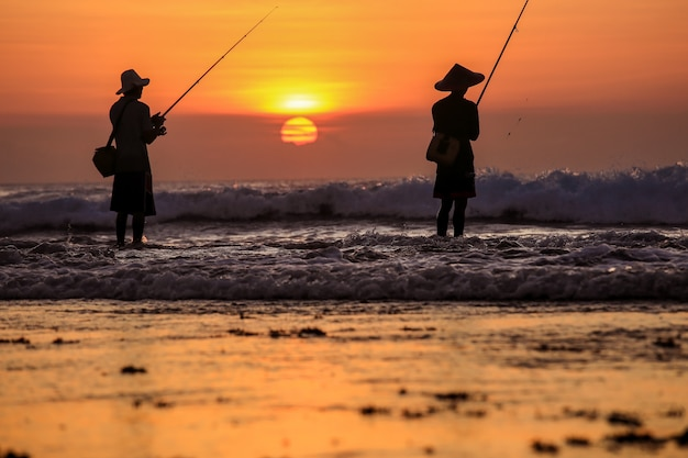 Silhouette of fishermen on the quiet ocean with the rays of sunset at jimbaran beach, bali, indonesia