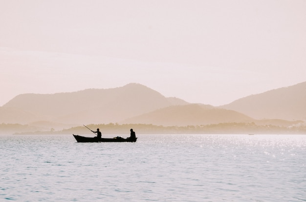 Silhouette of fishermen in a small boat