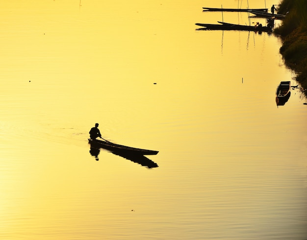 Silhouette of fishermen take a small fishing boat to the river at sunset yellow background