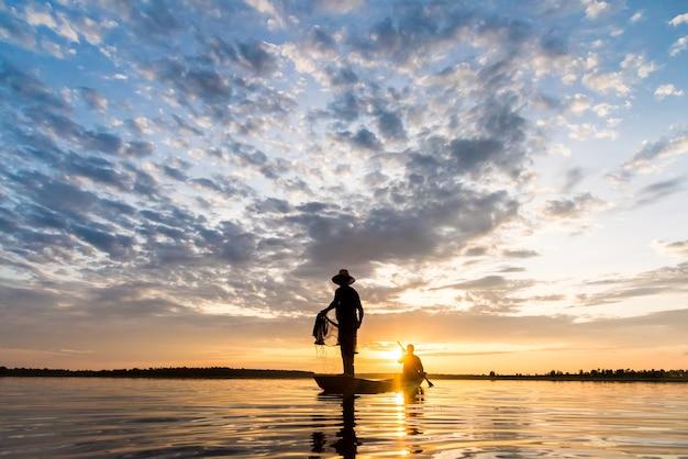 Silhouette of fishermen throwing net fishing in sunset time at wanon niwat sakon nakhon