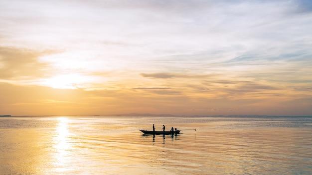 저녁에 일몰 하늘과 바다에 실루엣 낚시 보트