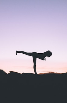 Silhouette of a fit woman practicing yoga on a high cliff at sunset