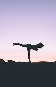 Silhouette di una donna in forma praticare lo yoga su un'alta scogliera al tramonto