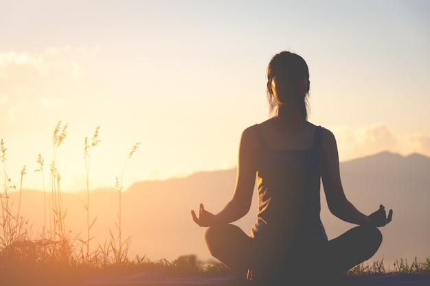 Йога девушки фитнеса силуэта практикуя на горе с светом солнца Premium Фотографии