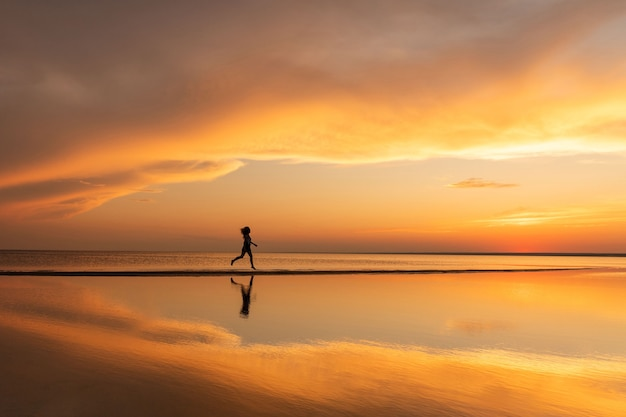 Silhouette of fitness woman running on the beach at sunset
