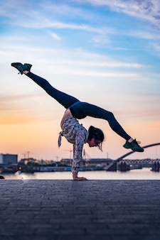 Silhouette of flexible female circus artist doing handstand on the dramatic sunset and cityscape con...