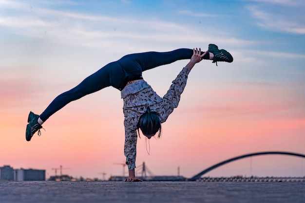 Silhouette of flexible female circus artist doing handstand on the dramatic sunset and cityscape. concept of individuality, creativity and outstanding.