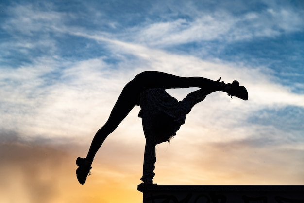 Silhouette of flexible female circus artist doing handstand on the dramatic sunset concept of indivi...