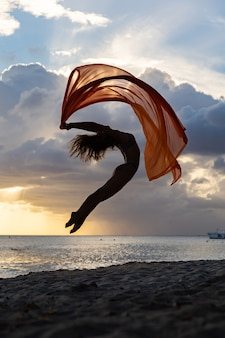 Silhouette of flexible fit woman jumping with silk during dramatic sunset with stormy clouds on the seascape background