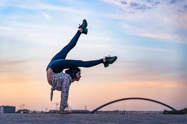 Silhouette of flexible woman doing handstand on the dramatic sunset and cityscape concept of individ...