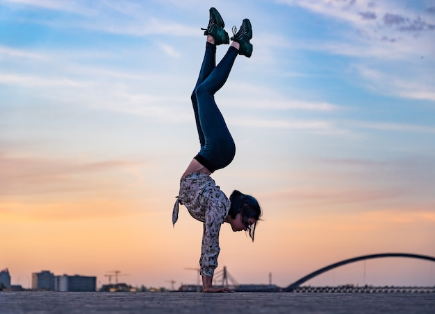 Silhouette of flexible woman doing handstand on the dramatic sunset and cityscape concept of willpow...