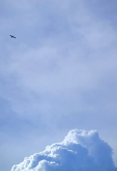 Silhouette of a flying airplane on bright blue cloudy sky with cumulus clouds