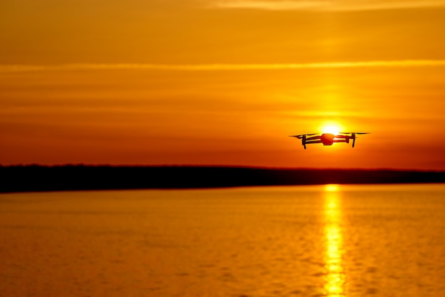 Silhouette of flying drone in glowing red sunset sky. elements of this image furnished