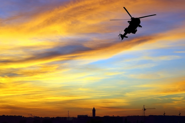Silhouette of a flying helicopter against the bright evening sky