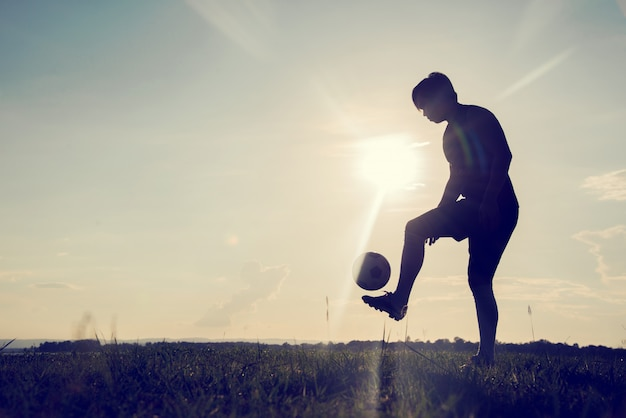 Silhouette of the football player with a soccerball against the sunset background.