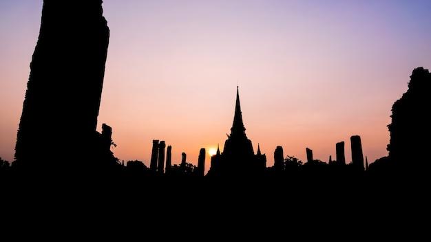 背景のシルエット、ワットプラシーサンペットの古い寺院の古代遺跡と塔日没時の有名なアトラクション、タイのプラナコンシアユタヤ歴史公園、16:9ワイドスクリーン