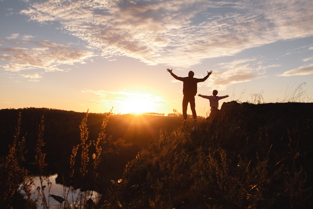 Silhouette of a free man and child enjoying freedom, feeling happy at sunset.