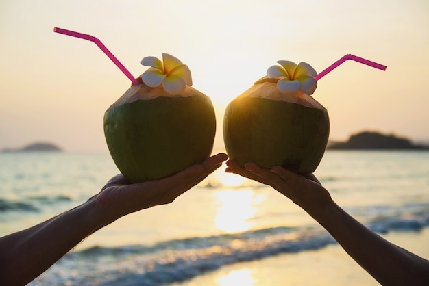 Silhouette of fresh coconut in couples hands with plumeria decorated on beach with sea wave - tourist with fresh fruit and sea sand sun vacation concept