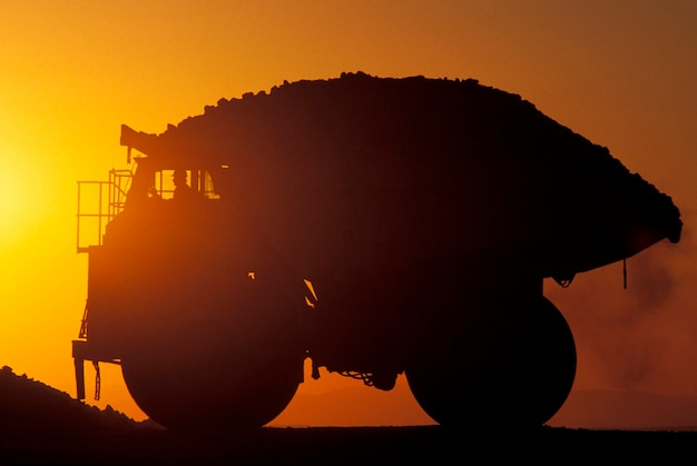 Silhouette of full dump truck with sunset in background