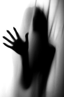 Silhouette of girl behind a curtain. abstract and blurred image of a girl