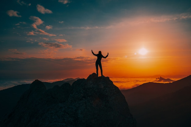 Silhouette of a girl dancing on top of a rocky peak at sunset