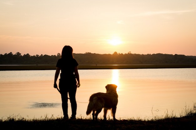 Silhouette of girl and dog golden on riverside