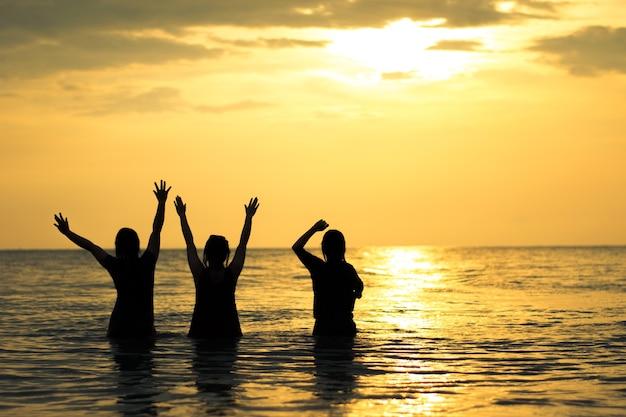 Силуэт девушка счастлива на море и закат небо на пляже таиланда