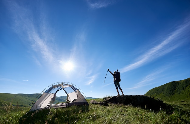 Silhouette of girl hiker with backpack standing on the top of a hill against blue sky, sun and clouds near tent, lifting hands up in the air with trekking sticks in hands, enjoying summer day